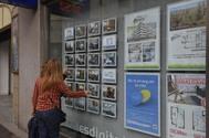 Unas mujeres miran unas ofertas de pisos en una inmobiliaria.