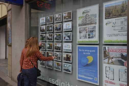 Dos jóvenes comprueban la oferta de pisos en una inmobilizaria de Vitoria.