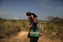 FILE PHOTO: A <HIT>Venezuelan</HIT> <HIT>migrant</HIT> carrying a baby walks along a trail into Brazil in the border city of Pacaraima