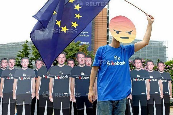 Un manifestante ondea una bandera de la Unión Europea junto a varias figuras de cartón con la imagen de Mark Zuckerberg en Bruselas.
