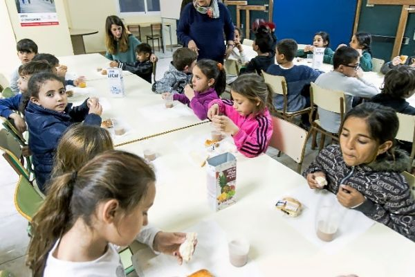 Niños disfrutando de sus vasos de leche.
