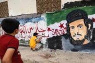 Un niño observa cómo se pinta un grafiti en homenaje al ex futbolista y miliciano rebelde Abdelbaset Sarut, en la localidad de Binnish (norte de Idlib).