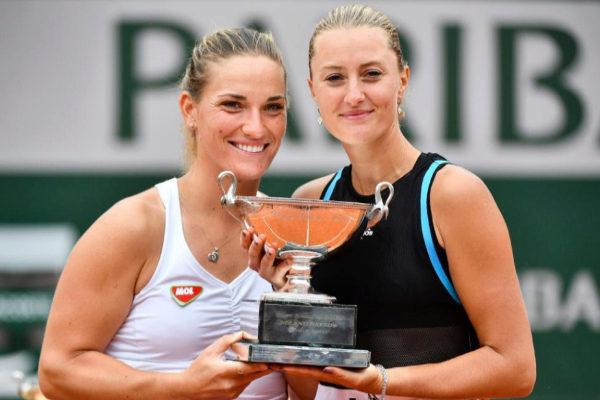 Kristina  Mladenovic (dcha.) y Timea Babos, con el título de dobles.