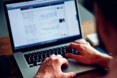 Un hombre consulta páginas web en internet en un ordenador portátil