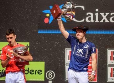Iker Iribarria posa con la copa y la 'txapela' aplaudido por Urrutikoetxea.