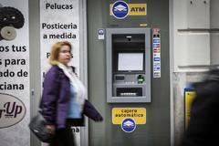 Una mujer camina por delante de un cajero bancario, en Valencia.