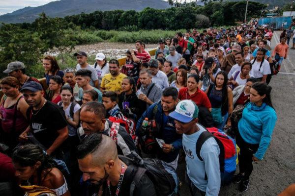 Decenas de personas hacen cola para cruzar el puente internacional Simón Bolívar, en la frontera entre Venezuela y Colombia.