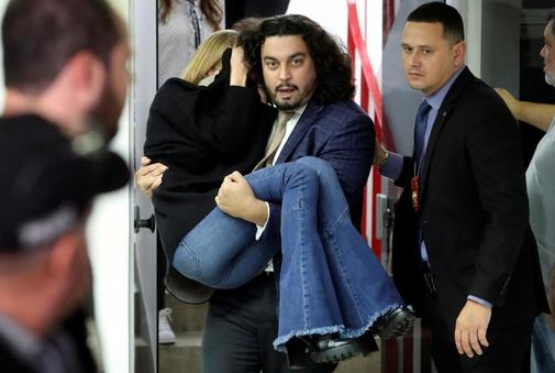 Najila Trindade de Souza, who accuses Brazilian soccer player <HIT>Neymar</HIT> of rape, is carried by her lawyer Danilo Garcia de Andrade after giving testimony in a police station, in Sao Paulo