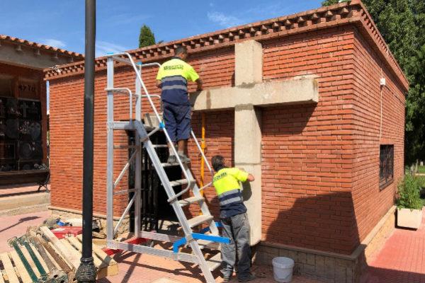 Unos operarios colocan la cruz del Calvario en el interior del cementerio.