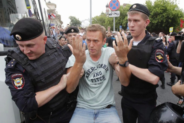 Policemen detain Russian opposition leader Navalny during a rally in...