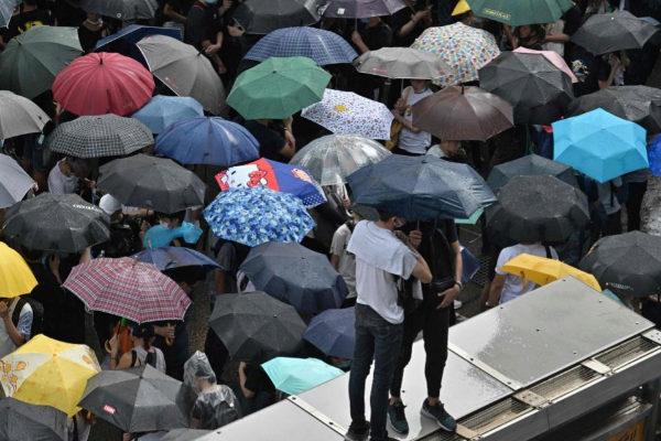 Los manifestantes se tapan con paraguas durante las protestas en Hong Kong.