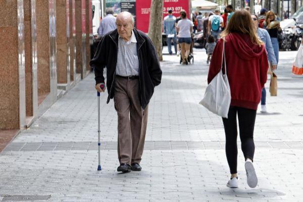 Un anciano camina solo por las calles de Barcelona.