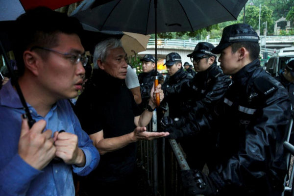Pro-democracy legislators react to riot police officers as they walk...