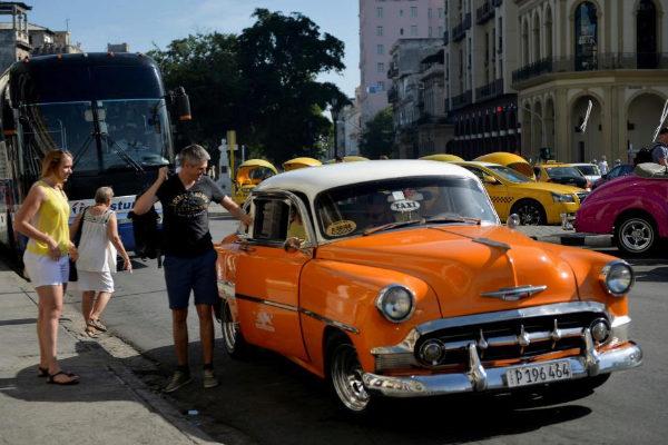 Turistas cogen un taxi en La Habana.