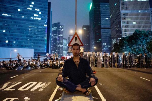 Un manifestante se sienta en el centro de la carretera tras las protestas en Hong Kong.