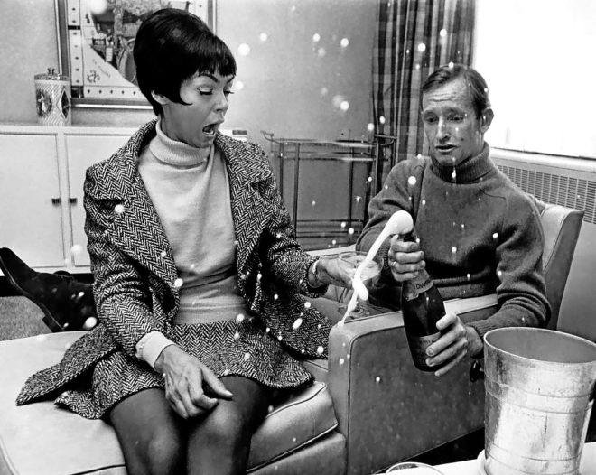 Una pareja celebra un encuentro íntimo descorchando una botella de 'champagne'.