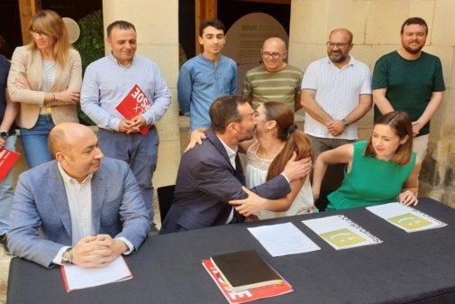 El alcalde Carlos González, y su socia, Mireia Mollà, se besan tras rubricar el acuerdo.