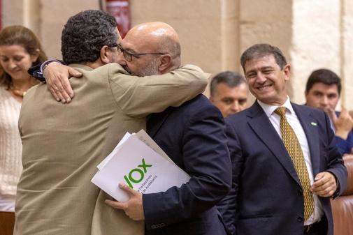 Los parlamentarios de Vox Francisco Serrano y Alejandro Hernández se abrazan tras la retirada de la enmienda a los presupuestos.