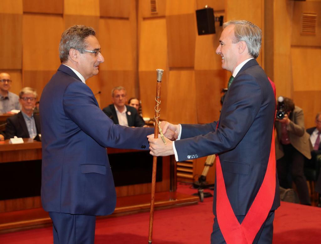 El candidato del PP Jorge Azcón (dcha.) recoge el bastón de alcalde de Zaragoza de manos del concejal de Vox Julio Calvo.
