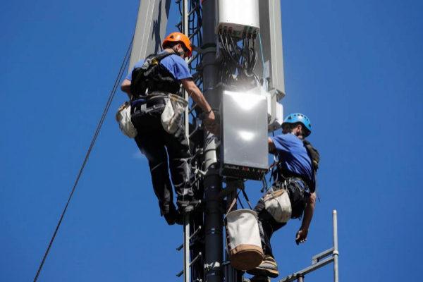 Dos técnicos instalan antenas de 5G en una torre de telecomunicaciones.