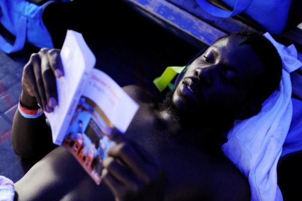Un inmigrante lee un libro a bordo del Aquarius.