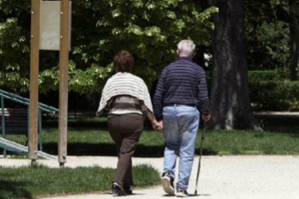 Una pareja de jubilados pasea por el parque del Retiro.