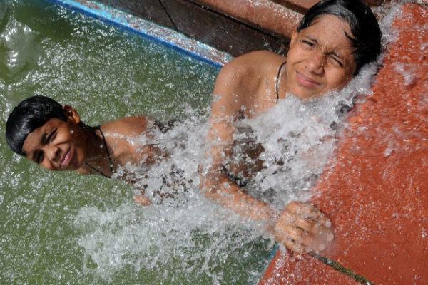 Dos niños indios se refrescan en una fuente en Nueva Delhi.