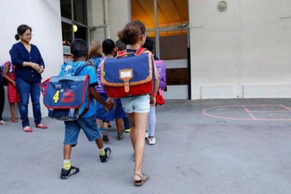 Varios niños entran a su primer día en un colegio.