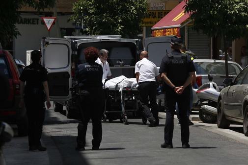 Agentes de la Policía Nacional observan el traslado del cadáver de la última víctima de violencia de género, en Córdoba.