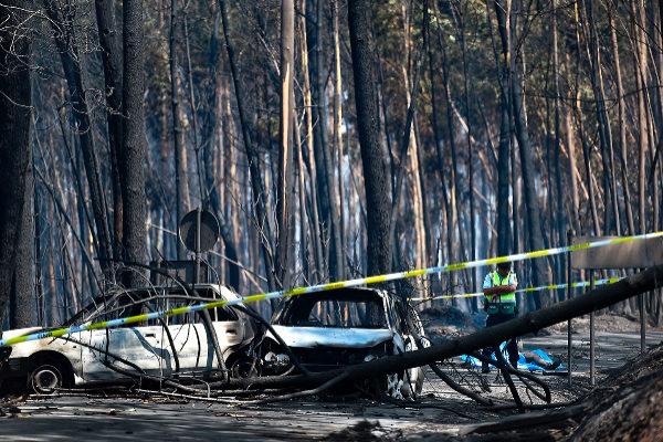 Un policía observa los daños del incendio junto a los cuerpo de una de las víctimas, en el bosque de Figueiro dos Vinhos, en 2017.