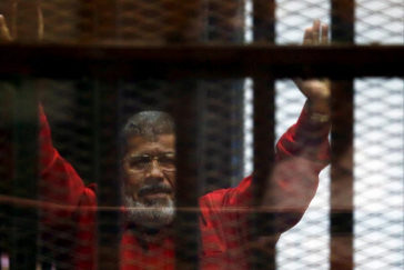 FILE PHOTO: Egypt's deposed president Mohamed <HIT>Mursi</HIT> greets his lawyers and people from behind bars at a court wearing the red uniform of a prisoner sentenced to death, during his court appearance with Muslim Brotherhood members on the outskirts of Cairo