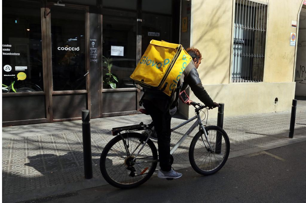 Un repartidor de Glovo circula en su bicicleta por las calles de Barcelona.
