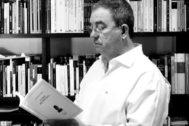 Parra Bañón leyendo su libro y mostrando su oído izquierdo a la cámara.