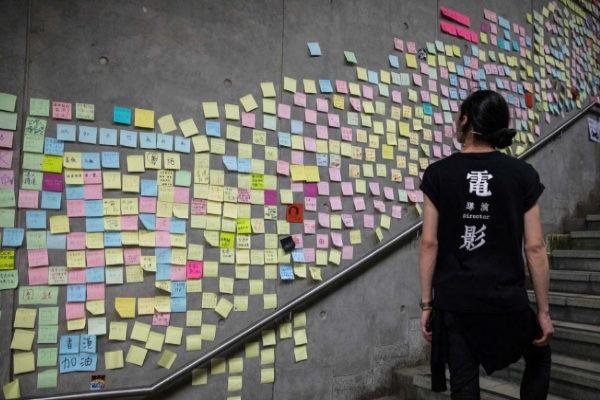 Una joven lee los cientos de mensajes dejados por los manifestantes en Hong Kong.ñ