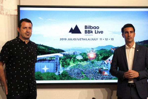 Alfonso Santiago, junto  al concejal de Bilbao, Xabier Otxandiano, ante el cartel del BBK Live.