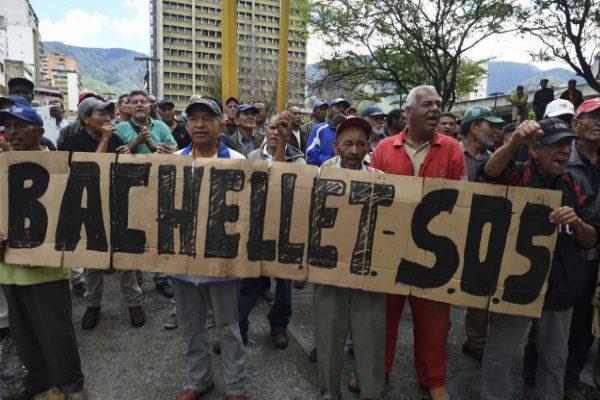 Trabajadores del sector petrolero, en huelga desde mayo, sostienen un cartel dirigido a Bachelet.