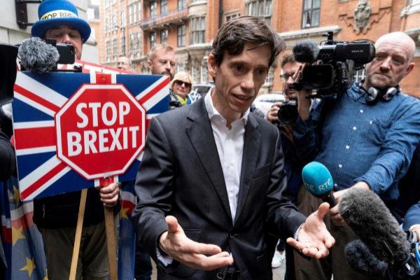 Rory Stewart realiza unas declaraciones para los medios ante un manifestante con una pancarta anti-Brexit.