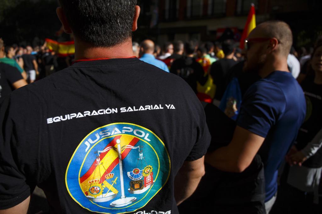 Un miembro de la Policía con una camiseta de Jusapol.