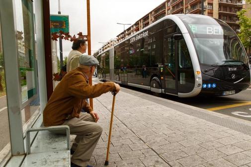 Dos ciudadanos observan al nuevo autobús eléctrico inteligente que ha circulado hoy por el centro de Vitoria.