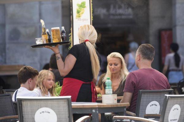 Una camarera sirve cerveza en una  terraza de la Plaza Mayor de Madrid.