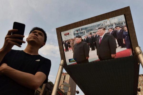 Una pantalla gigante muestra el encuentro entre Xi Jinping y Kim Jong Un.