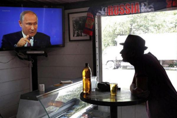 Un ciudadano sigue por televisión la tradicional Línea Directa anual  de Vladímir Putin.
