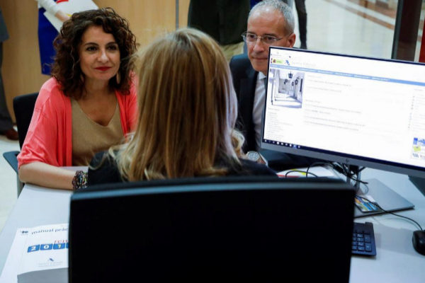 La ministra de Hacienda conversa con una funcionaria en una oficina de Hacienda