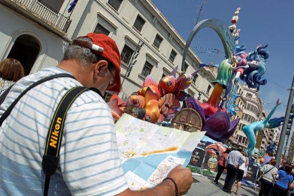 Un turista consulta un plano frente a una hoguera, este viernes en Alicante.