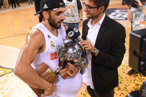 Campazzo atiende a un periodista con la Liga y el MVP.