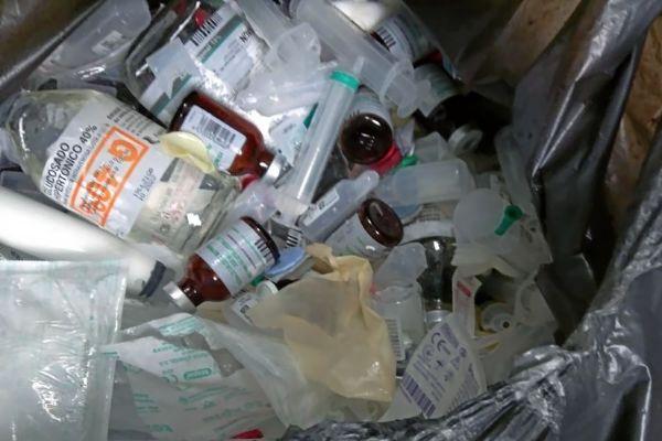 Bolsas de basura con botellas de cristal de los goteros mezcladas con frascos de pastillas y residuos plásticos y de papel.