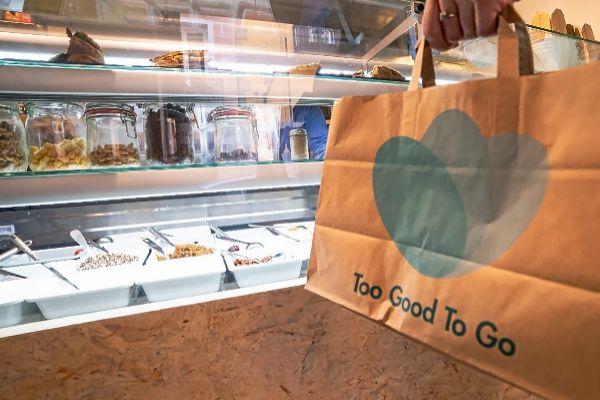 Una mujer recoge su pack sorpresa de comida adquirido a través de Too Good To Go en un establecimiento.