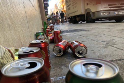Una de las calles del centro de Alicante, ayer por la tarde, llena de lastas de bebidas tras la mascletà.