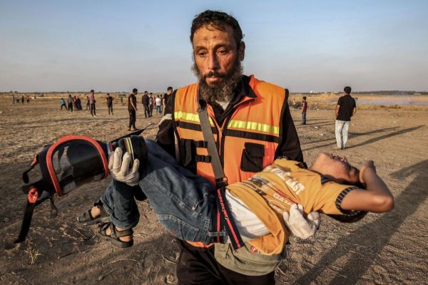 Un paramédico palestino lleva en brazos a un niño herido.
