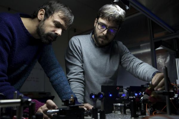 Dos investigadores trabajan en un laboratorio de óptica de Sevilla.